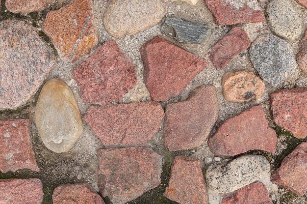 Pavimento de pedras de granito principalmente vermelho, padrão sem emenda, textura
