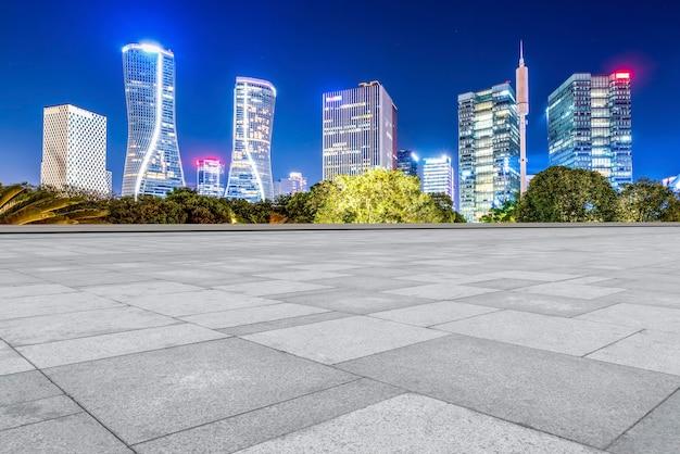 Pavimento de tijolos quadrados e cena noturna da arquitetura moderna