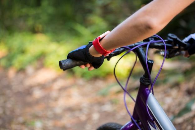 Pé atlético feminino com bicicleta de montanha no parque