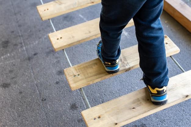 Pé da criança que faz equilíbrios em placas de madeira em um parque urbano da aventura.
