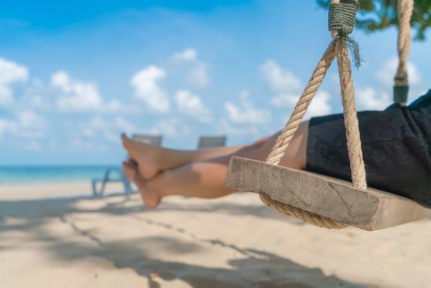 Pé da mulher em um balanço na praia do mar tropical