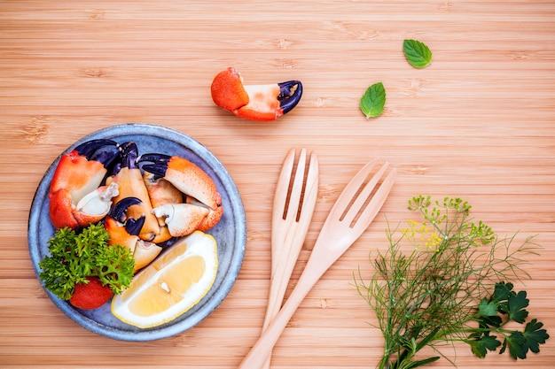 Pé de caranguejos vermelho cozinhado fresco na bacia com os ingredientes em placa de corte arborizada.