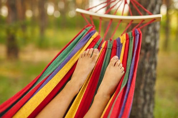 Pé de criança deitado na rede e relaxando em um dia ensolarado. descalço. conceito de estilo de vida.