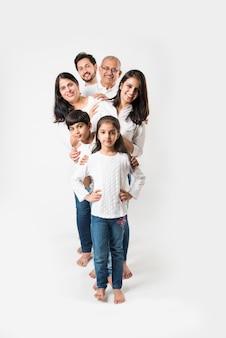 Pé de família indiana isolado sobre fundo branco. casal sênior e jovem com filhos vestindo jeans e blusa branca. foco seletivo