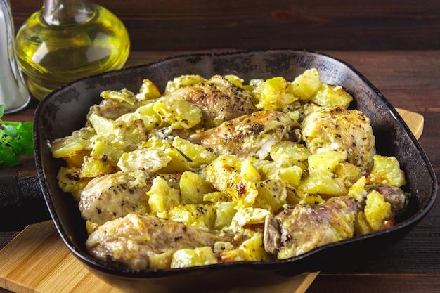 Pé de galinha roasted com as batatas com alcaravia e alho.