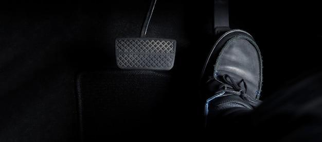 Pé de homem, acelerador e pedal de freio dentro do carro ou veículo e copie o espaço da cor preta