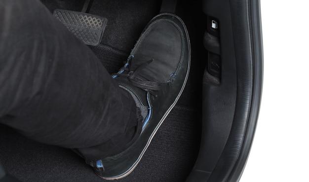 Pé de homem e acelerador e pedal de freio dentro do carro ou veículo e espaço de cópia que cor preta