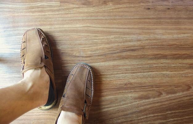Pé de homem usando sapatos de couro casual com piso de madeira.
