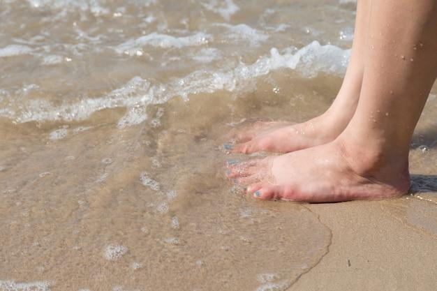 Pé de mulher na praia de areia com fundo de água do mar