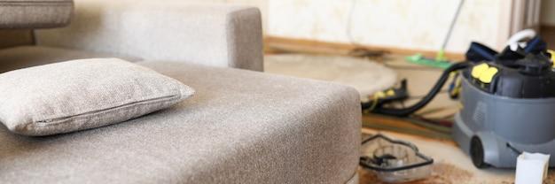Pé de sofá na sala doméstica com aspirador profissional em plano closeup
