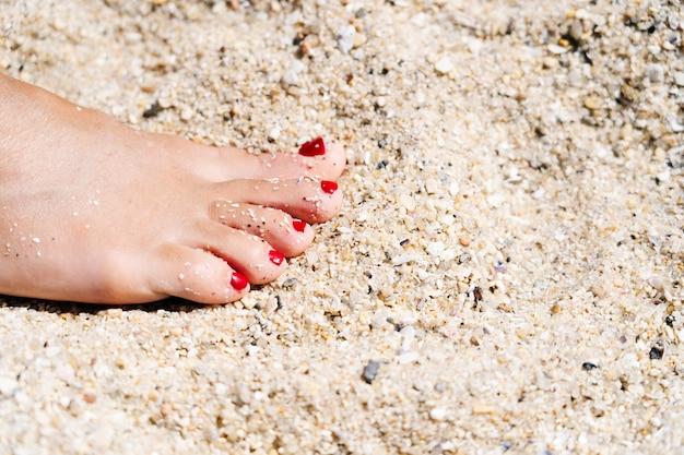 Pé de uma mulher na areia na praia