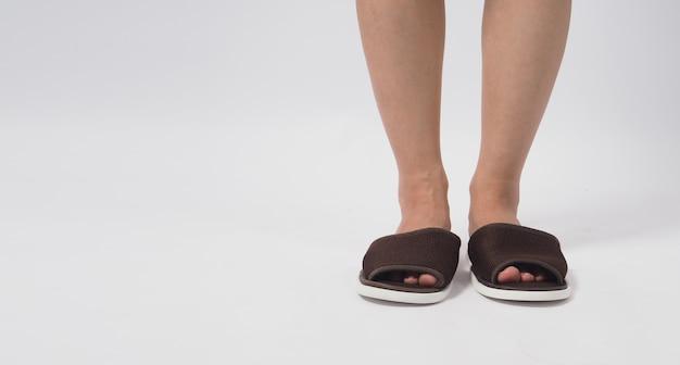 Pé feminino asiático e chinelo de desgaste isolado no fundo branco.