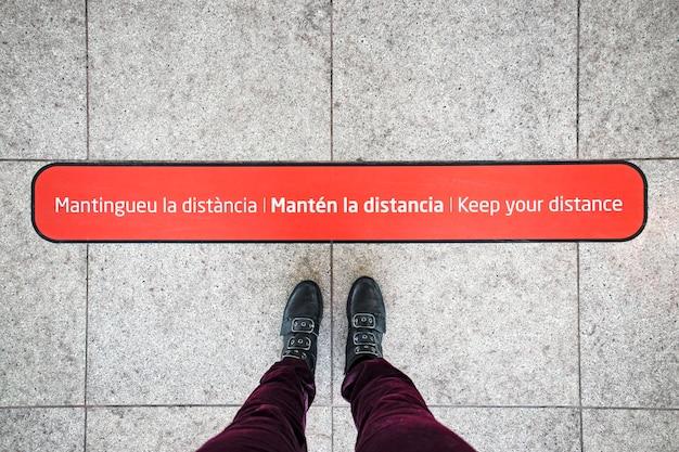 Pé feminino e sinal de distanciamento social no chão para passageiros em aeroporto internacional na espanha