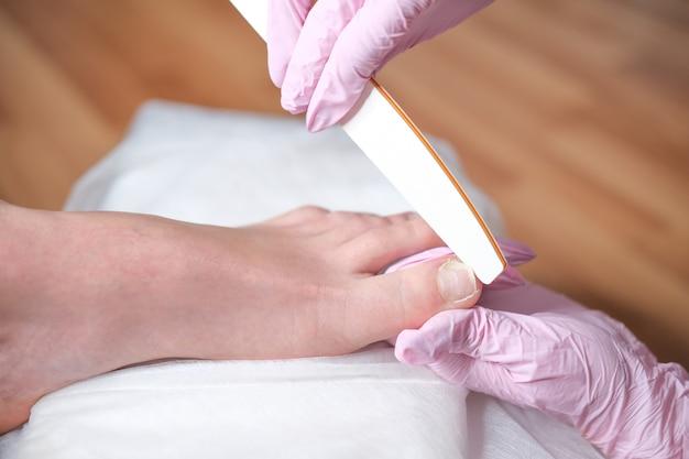 Pé feminino em processo de procedimento de pedicure em um close do salão de beleza. médico de podologia. tratamento de pés e unhas