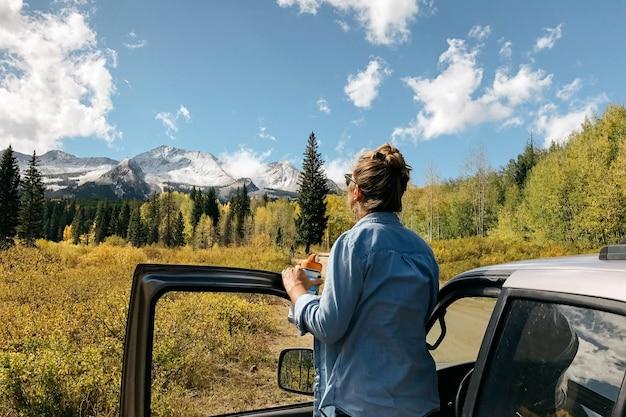 Pé feminino perto do carro, apreciando a vista com árvores e montanhas nevadas ao longe