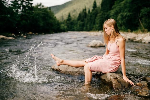 Pé jovem feliz, salpicos de água no rio