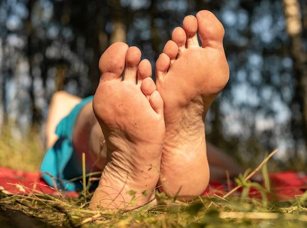 Pé masculino com salto na grama no verão ensolarado e bom tempo fecha o conceito de banho de sol