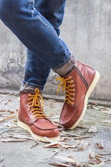 Pé masculino com sapatos de couro marrom e jeans