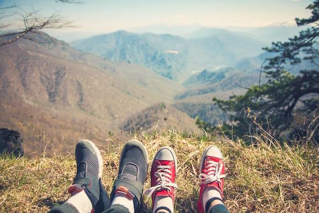 Pé menina e cara viajante que se senta no topo de uma montanha e olha para um platô de montanha.
