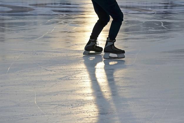 Pé patinando no gelo no rinque ao sol