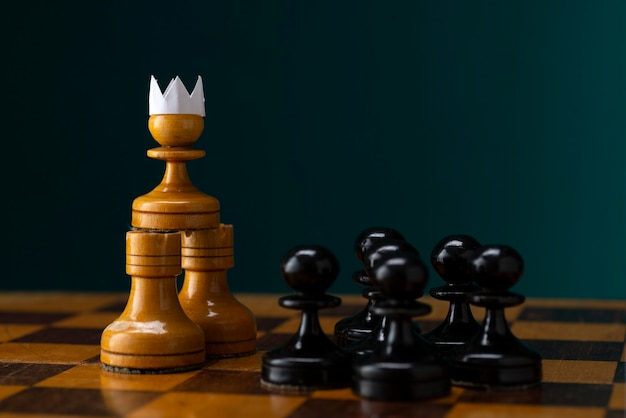Peão branco com uma coroa de papel na frente de um exército de peões pretos