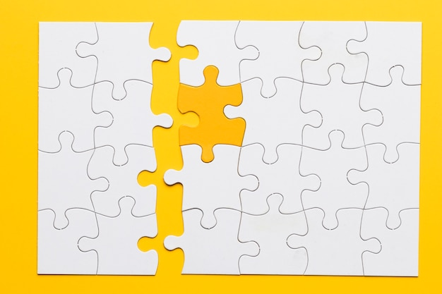 Peça amarela conectar-se com peças de quebra-cabeça branca no fundo liso