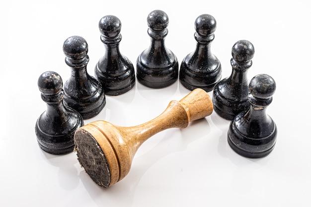 Peça caída do rei do xadrez cercada pelos peões, metáfora da mudança de regime