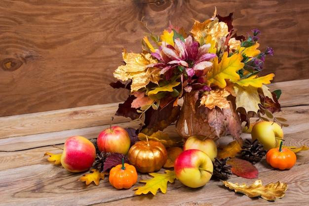 Peça central da mesa de ação de graças com abóbora dourada e folhas