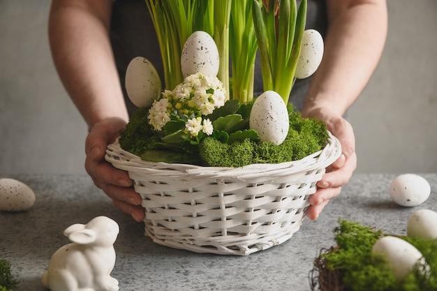 Peça central da mesa de páscoa diy com ovos festivos, musgo e coelho. composição de primavera. oficina floral.