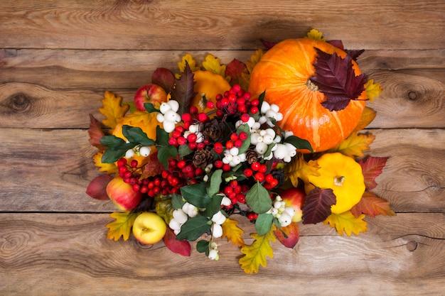 Peça central de ação de graças com snowberry e abóboras em fundo de madeira