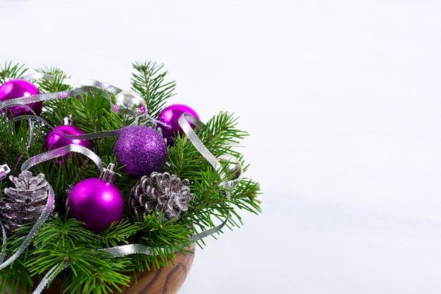 Peça central do natal com cones de glitter e ornamentos roxos, copie o espaço.