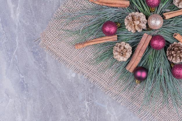 Peça central feita de galhos de carvalho e cones com bolas e paus de canela.