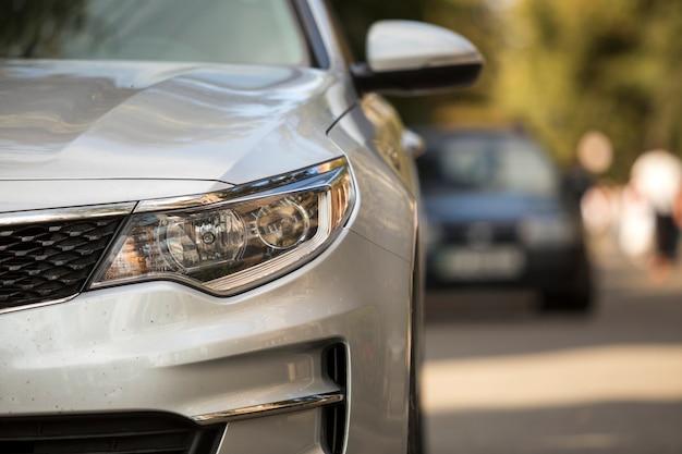 Peça de detalhe close-up de prata brilhante carro-pára-choques, farol, roda e grade do radiador no exterior turva