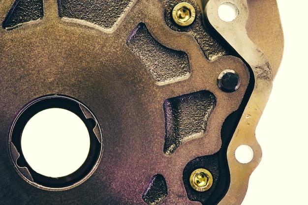 Peça de metal com furo redondo e parafusos close up