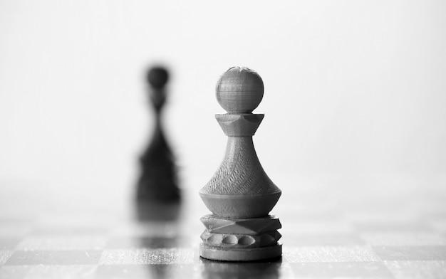 Peça de peão de xadrez a bordo em fundo branco