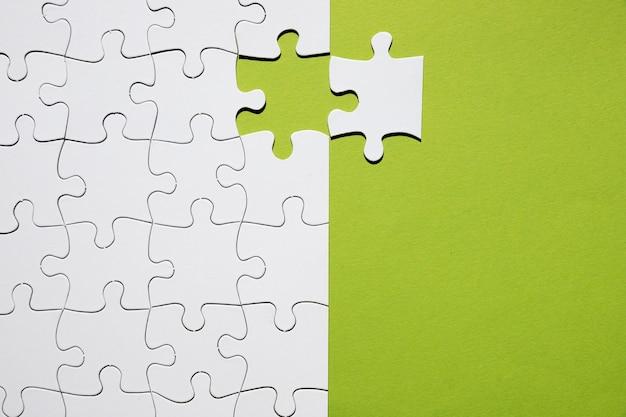 Peça de quebra-cabeça branca separada com grade de quebra-cabeça branca no pano de fundo verde