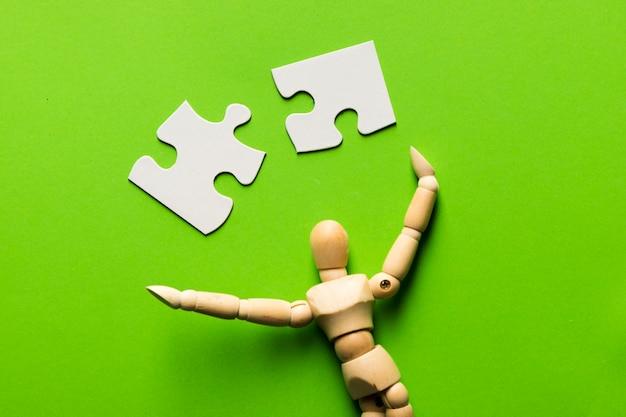 Peça de quebra-cabeça com figura humana de madeira no pano de fundo verde