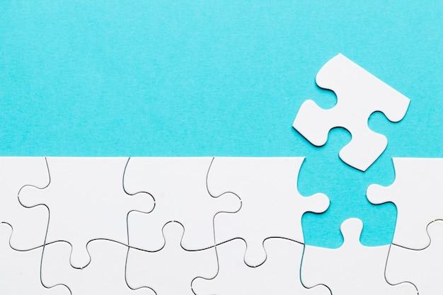 Peça de quebra-cabeça faltando com grade de quebra-cabeça branca sobre fundo azul