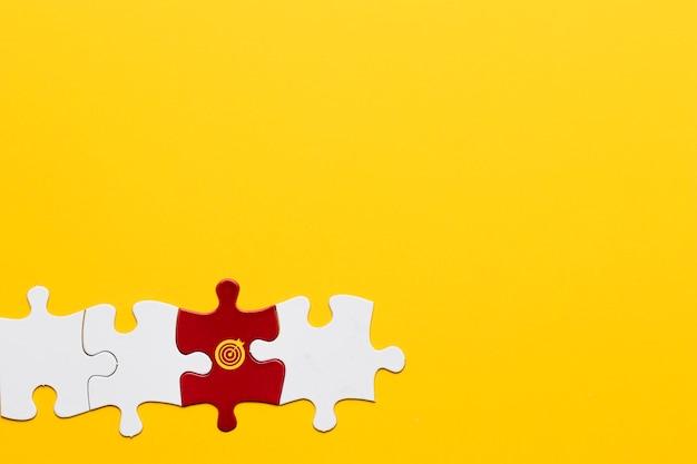 Peça de quebra-cabeça vermelha com símbolo de dardos, disposta com uma peça branca em fundo amarelo