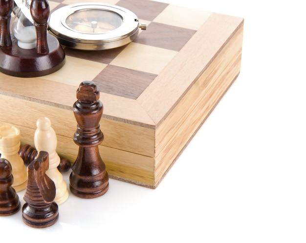 Peça de xadrez, bússola e vidro de areia a bordo isolado no fundo branco