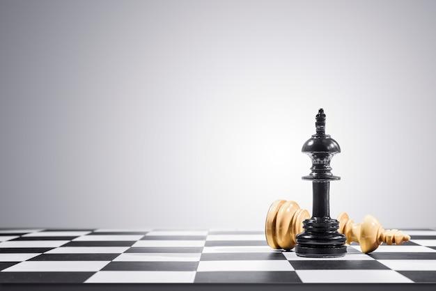 Peça de xadrez de rei marrom derrotada por peça de xadrez de rei preto