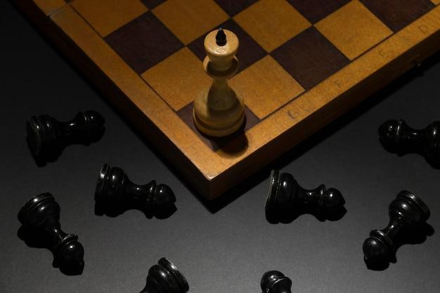 Peça de xadrez do rei branco com peças pretas caídas. conceito de sucesso