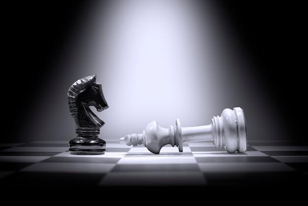 Peça de xadrez do rei branco derrotando por peça de xadrez de cavaleiro negro