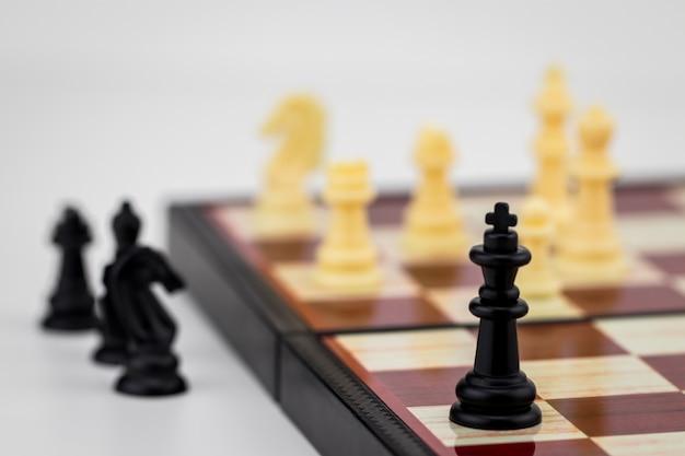 Peça de xadrez do rei com figuras de xadrez em pé.