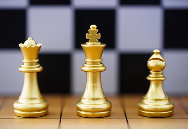 Peça de xadrez do rei de ouro e várias peças de xadrez em um tabuleiro de xadrez de madeira, conceito de jogo de liderança de estratégia