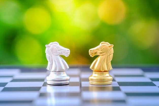 Peça do cavaleiro da xadrez do ouro e da prata no tabuleiro de xadrez.