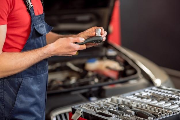 Peça sobressalente. mãos experientes de mecânico de automóveis em macacão azul com peça sobressalente acima da gaveta aberta