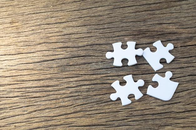 Peças brancas de quebra-cabeça mentem sobre uma mesa de madeira