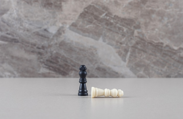 Peças brancas e pretas do rei do xadrez em mármore
