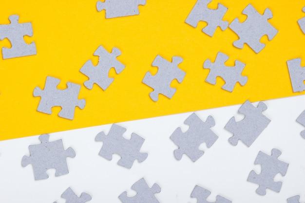 Peças cinza do quebra-cabeça isoladas em branco e amarelo